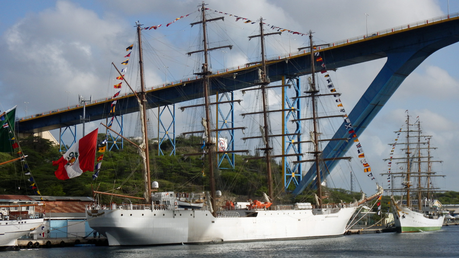 Tall ships line St Anna Bay Channel under the Queen Juliana Bridge, Curaçao