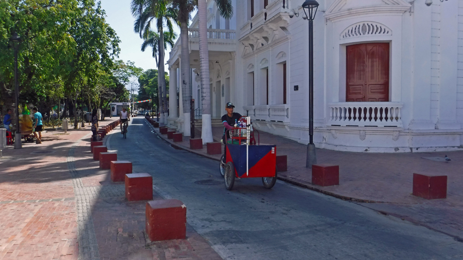 An icee vendor cycles his cart past the Palacio de Justicia - Justice Offices