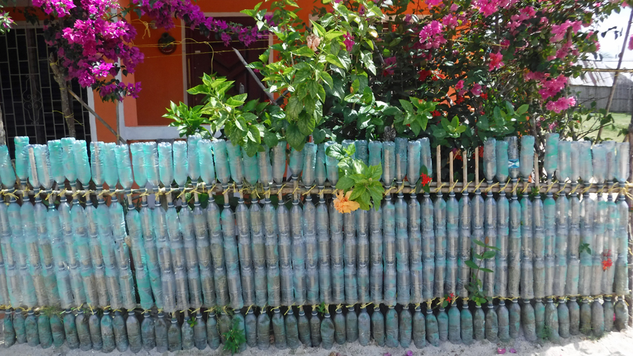 "A fence made of plastic bottles brings to mind the song, ""100 bottles of beer on the wall...."""